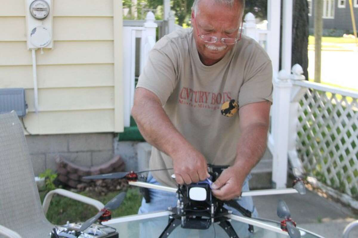 Areaux attaches a battery to the Turbo Ace Infinity Six drone before taking it out to fly it on Monday. He often flies his drones at parks in Manistee such as Morton Park. (Sean Bradley/News Advocate)