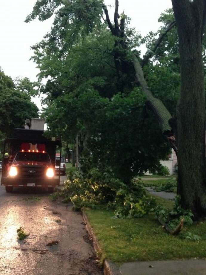 City of Manistee Department of Public Works employees worked on Sunday night after a storm to clean up debris from a tree damaged by wind at a home on Second Street in Manistee.
