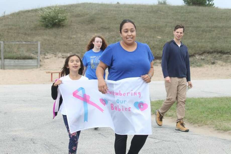 "The 2016 Walk to Remember Saturday at Manistee Catholic Central had about 35 people walking in honor of lost infants due to stillbirth, miscarriage or early infant death. Ava (left) and her mother Angelina Anderson carried a banner throughout the walk which read ""Remember Our Babies."" (Sean Bradley/News Advocate)"