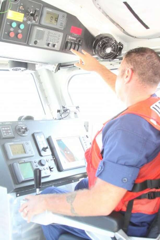 Andrew Gyurscik, officer in charge of the Coast Guard Station Manistee, captains the 45-foot response boat medium during a search-and-rescue exercise Friday off the shores of First Street and Fifth Avenue beaches. Members of the U.S. Coast Guard Station Manistee rescued a man from the water by sending a team member into the water to retrieve him while others on the boat work to bring them both to safety. (Sean Bradley/News Advocate)