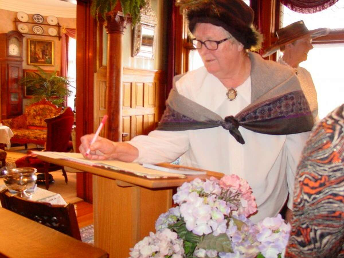 Carol Voigts signs in as she arrives at the first Mary Mullen Dempsey ladies tea on Oct. 25 at the James Dempsey Mansion in Manistee. (Courtesy photo)