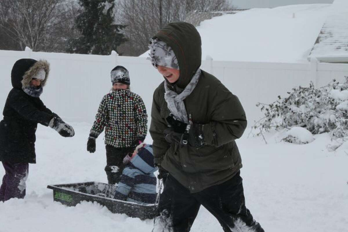 Dylan Madsen, 10, pulls his brother Monty, 3, on a sled Tuesday afternoon while Ruby Madsen, 6, and Evelyn Koller, 8, look on. (Dylan Savela/News Advocate)