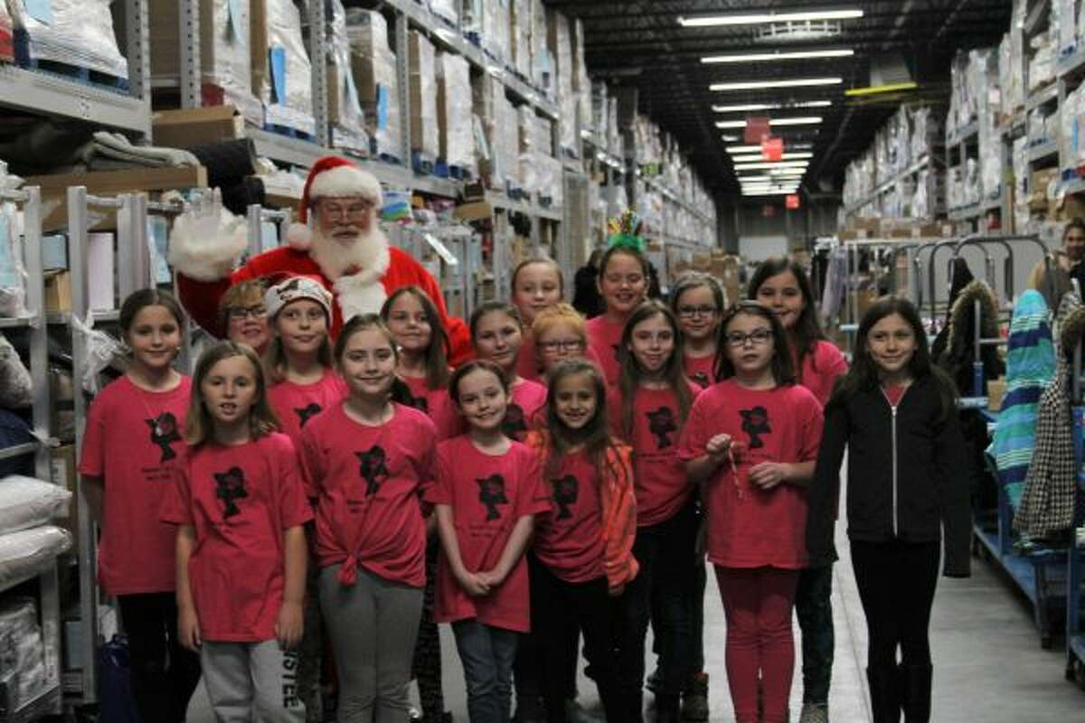 Ladies First of Kennedy Elementary pose for a photo. They were helping wrap gifts at the event on Thursday. (Ashlyn Korienek/News Advocate)