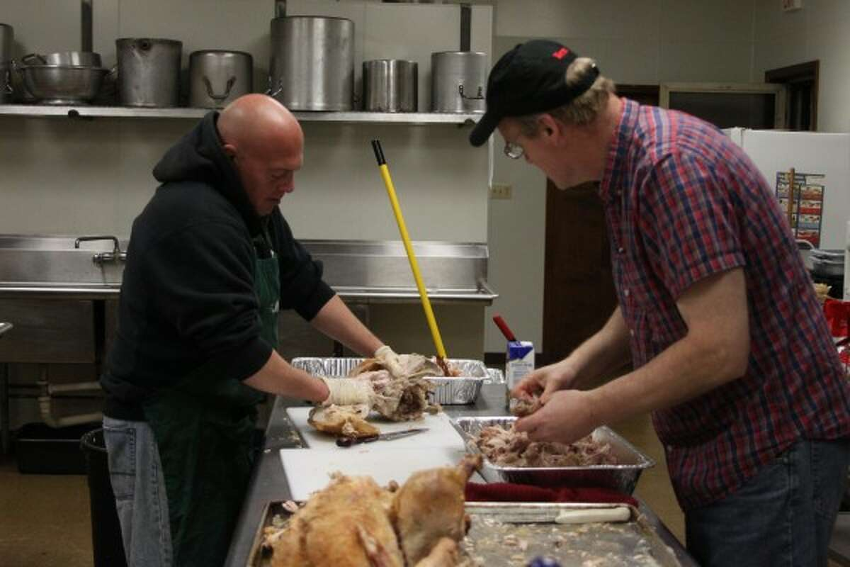 Jim Naffie (left) and Joe Bigalke (right) prepared the turkeys the day before Thanksgiving to be served. Naffie took over hosting and organizing the dinner after his mother, whom the dinner is named after, passed away in 2011. (Sean Bradley/News Advocate)