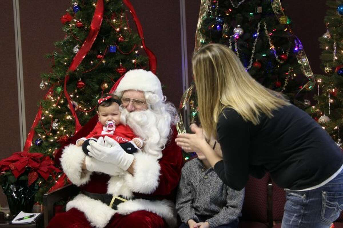 Tiffany Wotnow, of Manistee, takes a picture of her niece Mila on Santa's lap on Saturday at the Manistee County Senior Center's Breakfast with Santa event. (Sean Bradley/News Advocate)