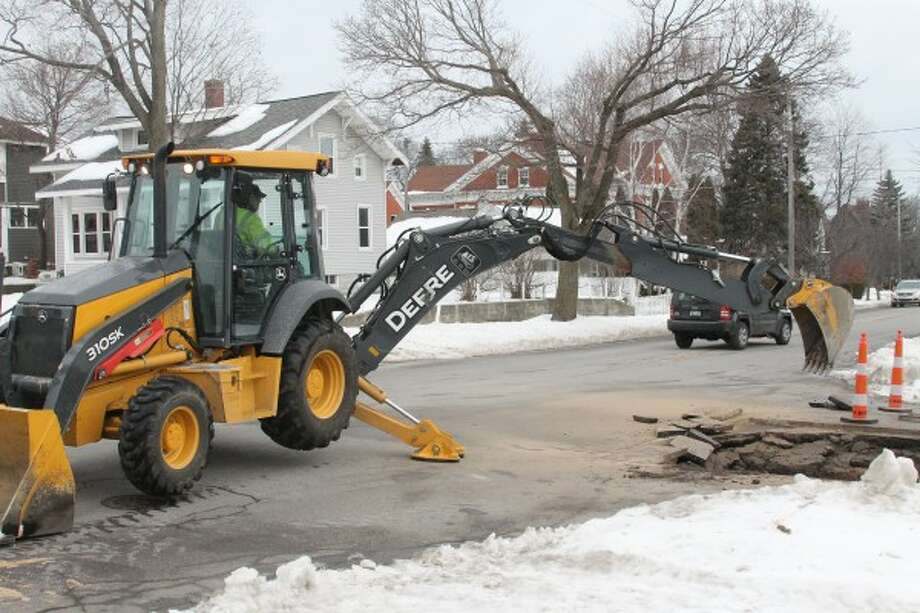 Bobby Niesen, an employee of the City of Manistee Department of Public Works, operates an excavator on Friday during the repair of a water main break at the corner of Third and Maple streets in the city. (Sean Bradley/News Advocate)