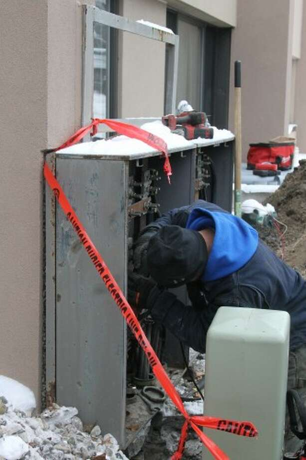 An employee of Top Line Electric works toward installing a new power transformer on Thursday at Century Terrace Apartments in Manistee. The replacement of the transformer — the old transformer failed last fall — left residents without power and heat throughout the day, however generators and heaters were set up by the Manistee Housing Commission and the Manistee public safety officials checked on residents with medical needs. The transformer was scheduled to be down for about 12 hours. (Sean Bradley/News Advocate)