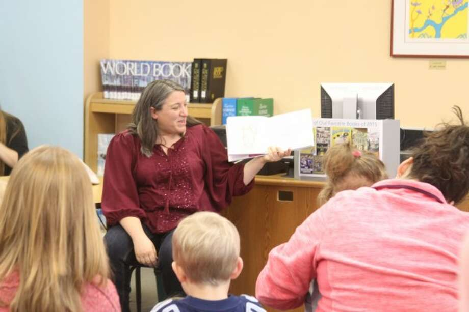 Andrea Cosier, the Manistee County Library's children's librarian, read two stories to the children. While reading the stories, Cosier asked the children questions about the story and what would happen in it next. (Sean Bradley/News Advocate)