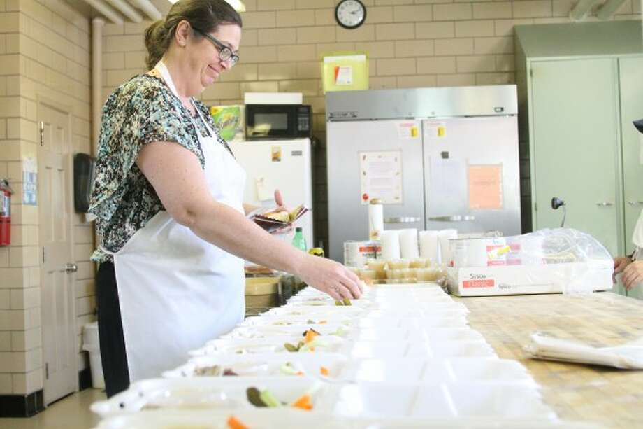 Ann Lind, organizer of the Trinity Lutheran Church and School's Roast Pork and Sauerkraut Supper, puts bread rolls in to-go boxes on Saturday, just a few hours before the event began. Last year, 152 take out orders were served, and between 600 and 700 people are served annually. (Sean Bradley/News Advocate)