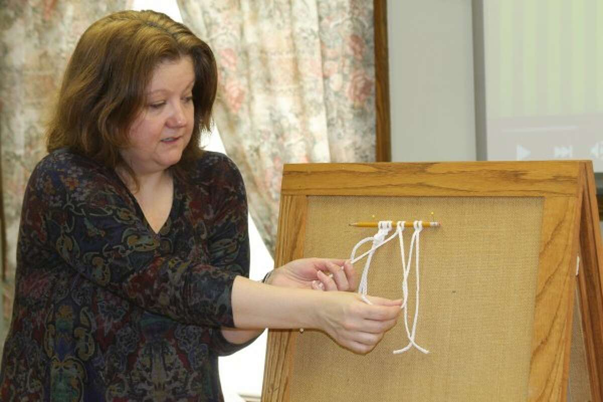 Kim Jankowiak, reference librarian, teaches a group how to tie knots during a beginning macrame crafting class on Saturday at the Manistee County Library. (Michelle Graves/News Advocate)