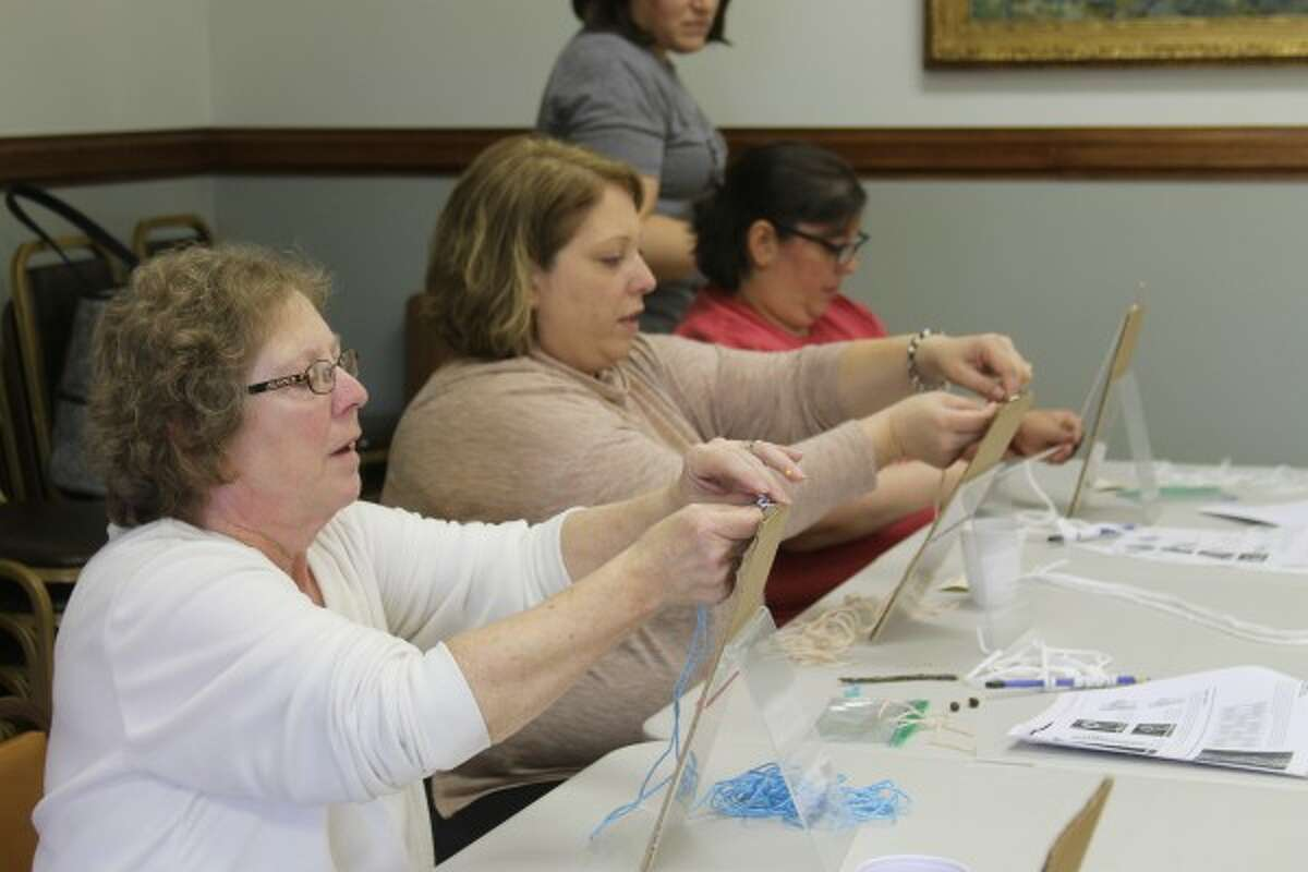 (From left) Jean Vasquez, Lisa Senters and Cindy Vasquez, all of Manistee, learn how to make a key chain owl using macrame at the Manistee Library on Saturday. (Michelle Graves/News Advocate)