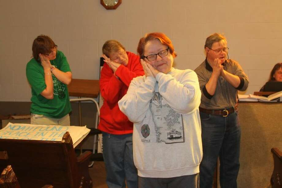 Pam Bresnahan, (front) Circle Rocking S Children's Farm board member, leads the children's choir in singing a song on Monday during their weekly rehearsal. (From left) Katie Huggard, of Scottville, Sheryl Kuenzer, of Manistee, and Paul Vadebonceur, of Manistee, are members of the choir. (Michelle Graves/News Advocate)