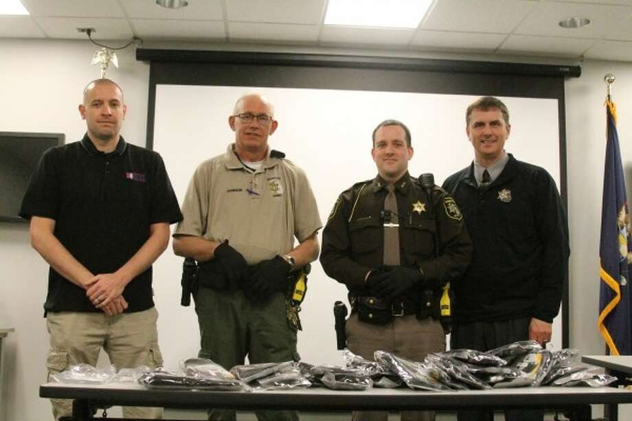 Manistee County Jail corrections officer Jim Johnson (middle left) and Sheriff's Office deputy Travis Wheaton (middle right) show off the gloves the sheriff's office obtained via a Michigan Counties Workers' Compensation Fund grant. Assistant jail administrator Sgt. Chris Banicki (far left) and undersheriff John O'Hagan (far right) were also present. (Sean Bradley/News Advocate)