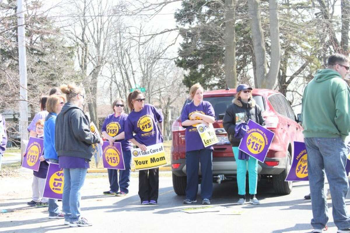 About 30 people, many of them employees of Service Employees International Union (SEIU) Healthcare Michigan-represented facilities in Manistee, marched and chanted Thursday in favor of a $15 minimum wage in Michigan. (Sean Bradley/News Advocate)