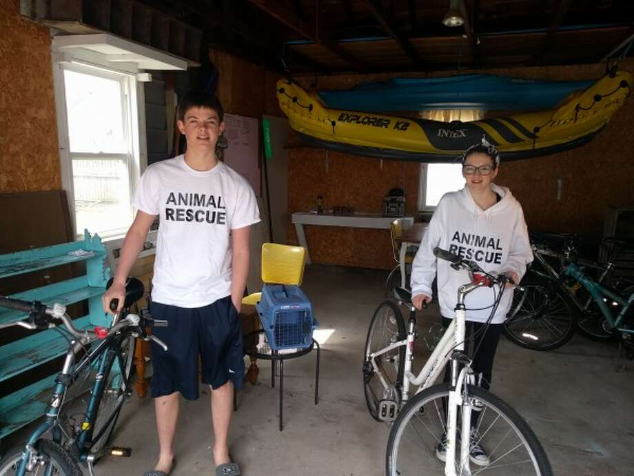 """With """"Animal Control"""" shirts on, Keaton Connell, 14, and his sister McKenna, 13, started an animal rescue operation in 2013, saving six cats and three dogs last year. Seasonal residents from Cicero, Ind., they plan to continue their operation this year when in Manistee by working closer with Spay and Neuter Action Group (SNAG). (Courtesy Photo/News Advocate)"""