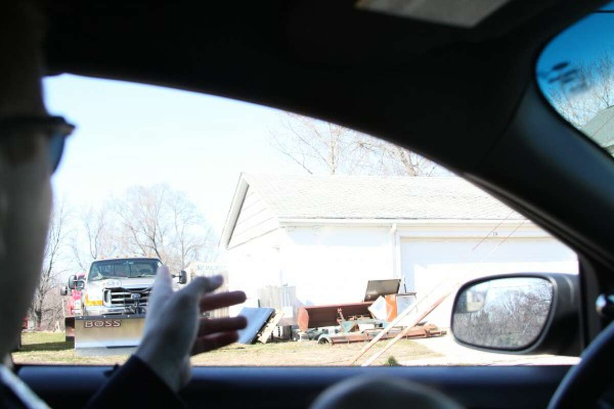 Manistee police officer John Fraass points out blight at a garage on Ninth Street in Manistee. He said the state defines blight as anything that lowers an affected property's value or that of any surrounding properties. (Sean Bradley/News Advocate)