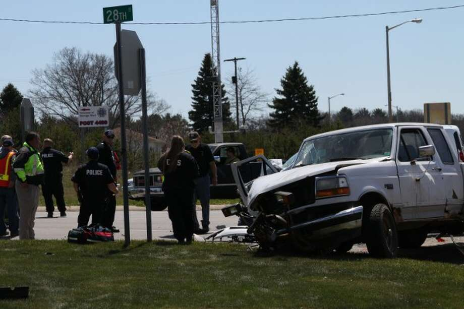 Local officials investigate an accident scene Tuesday at the intersection of U.S. 31 and 28th Street in Filer Township. The accident sent three people to West Shore Medical Center with different levels of injury. (Sean Bradley/News Advocate)