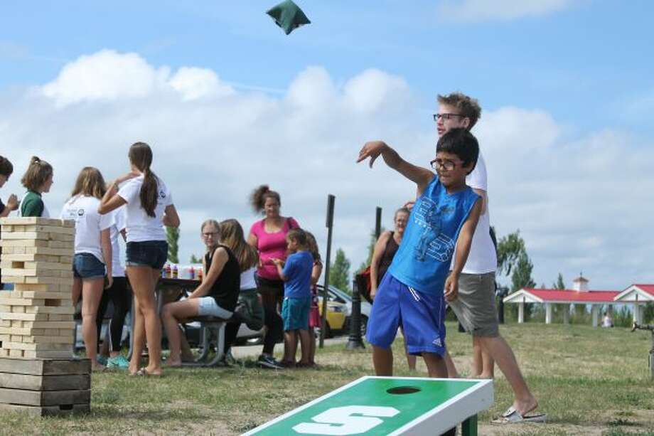 Vincent Leon, 8, plays cornhole at the United Way community picnic on Wednesday afternoon. (Dylan Savela/News Advocate)