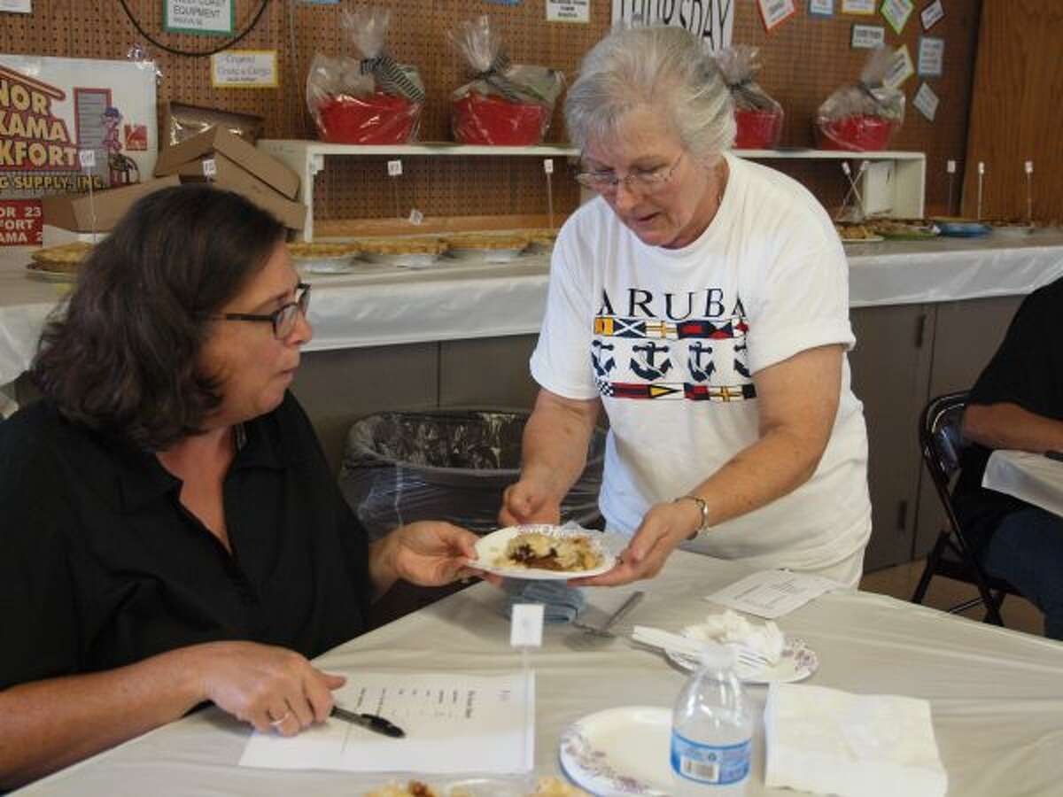 Bev LeSarge hands a pie to judge Ann Lind during the Pie Baking Contest at the Manistee County Fair on Thursday.