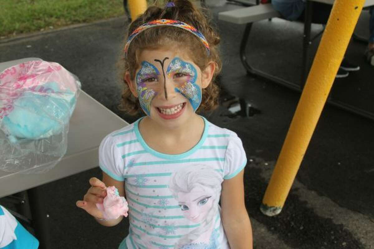 Allison Ladd, 6, of Manistee, enjoyed cotton candy on Saturday after having her face painted at the Manistee County Fair.