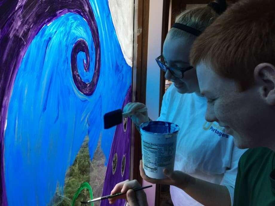 Freshmen Alliyiah Torrey and Kolin Kook paint the windows of One Kama Mama's Pizza in downtown Onekama. (Courtesy photos)