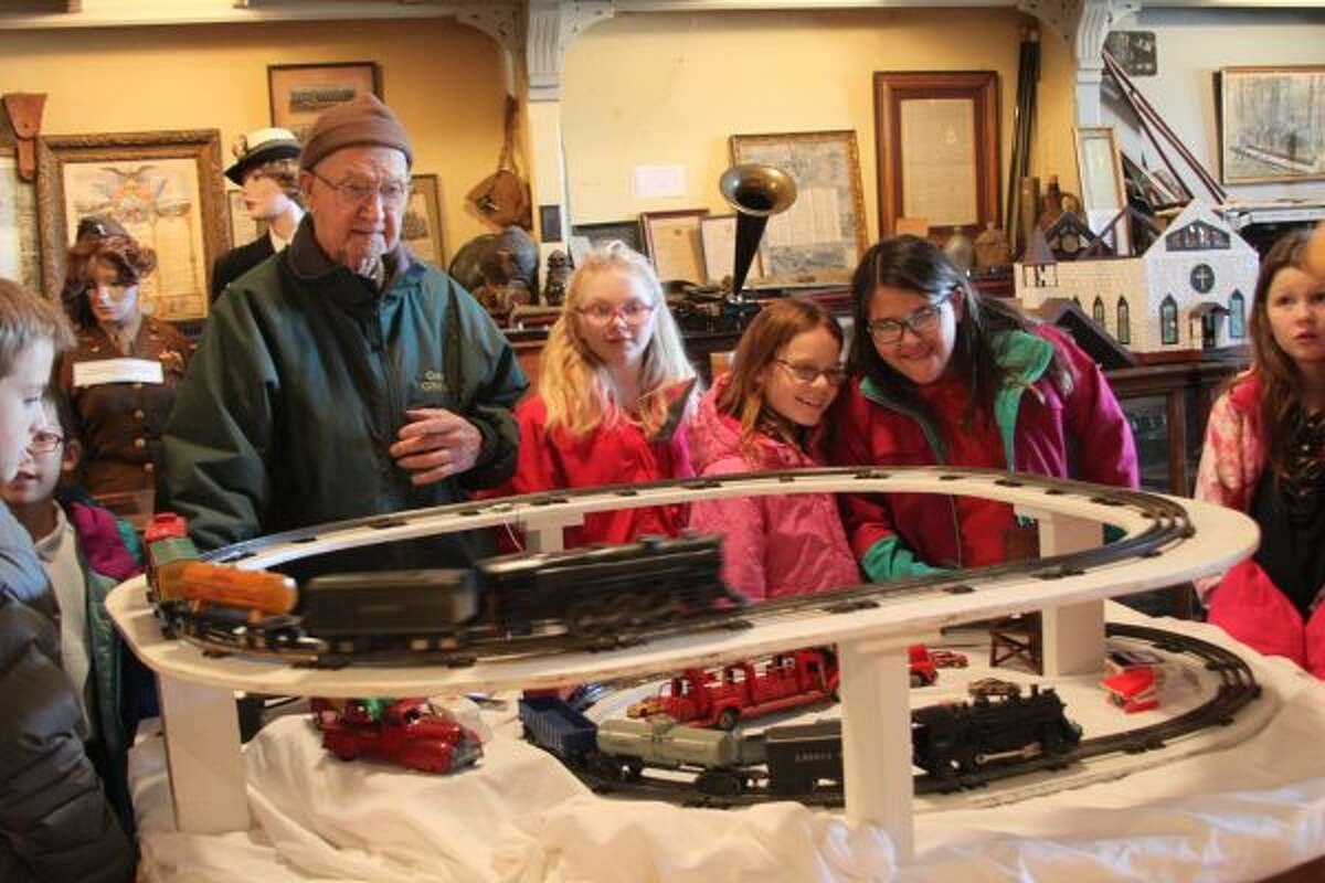 Manistee County Historical Museum volunteer Ray Fortier shows off the trains to students from Manistee Catholic Central during their visit to the museum on Tuesday. (Michelle Graves/News Advocate)