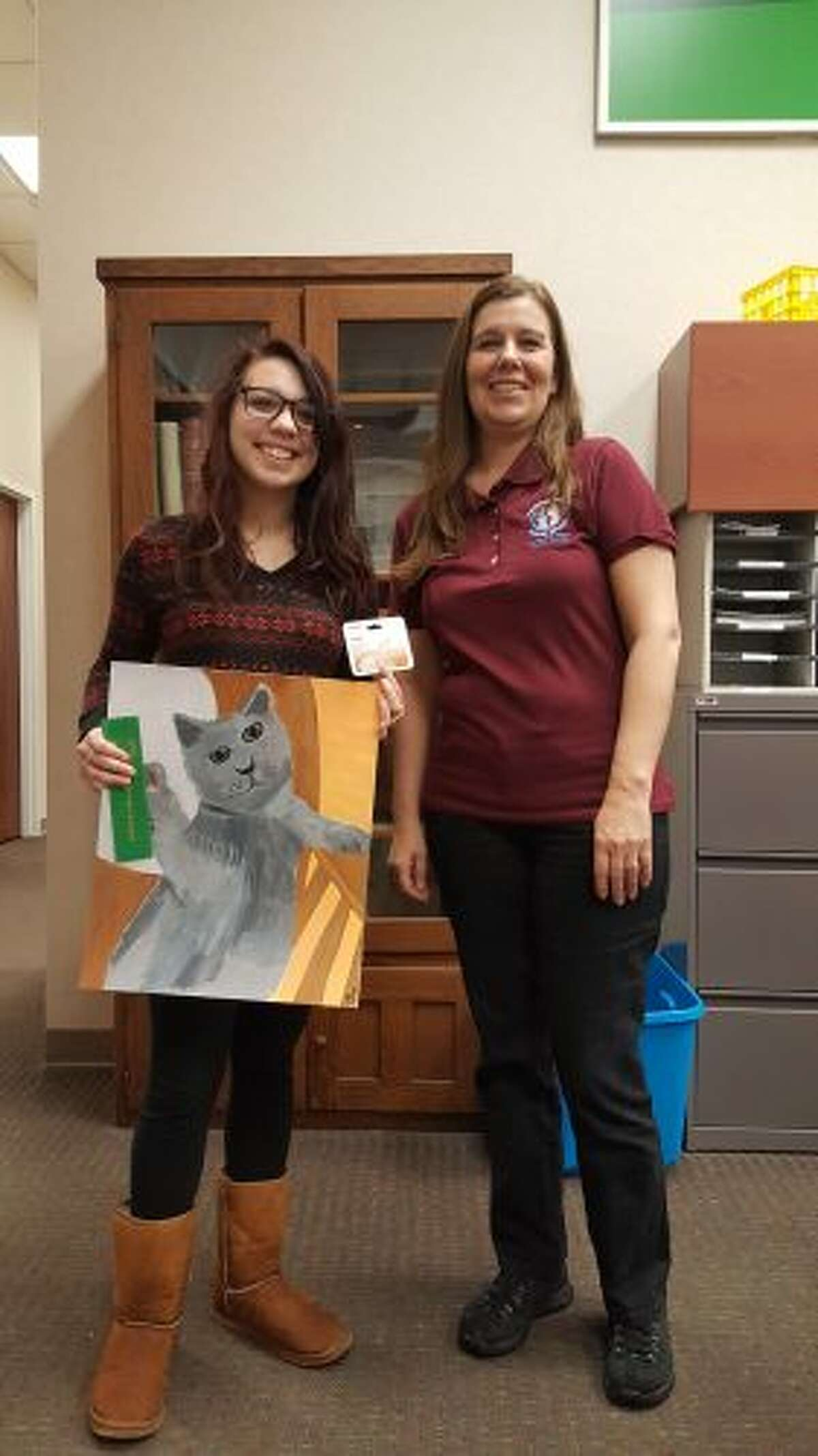 Homeward Bound Animal Shelter manager Shareen Edmondson (right) presented Cayenne Lasecki, of Manistee High School, with her prizes for the shelter's pet contest. (Courtesy photos)
