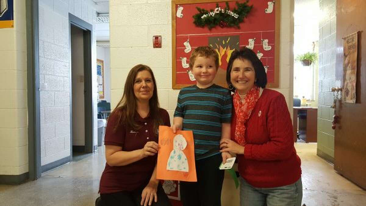 Emmett Johnson, of Madison Elementary School, shows off the picture his drew for the Homeward Bound Animal Shelter contest. Shelter manger Shareen Edmondson (left) presented him with a ribbon and gift card.