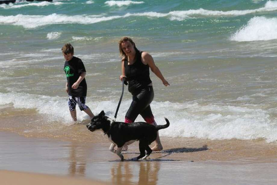 Isaac, his mother Alicia Dore and their dog, Forrest all jumped in Lake Michigan on Saturday for the Chilly Dawg Dunk. (Michelle Graves/News Advocate)