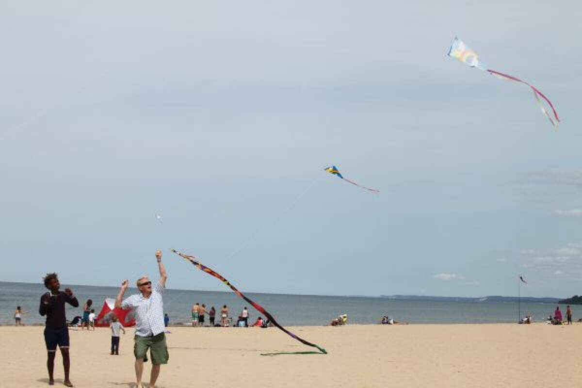 Dave Anderson (right) helps Ranson Hoeflinger with his kite on Saturday during Kite Day at Fifth Avenue Beach. (Michelle Graves/News Advocate)