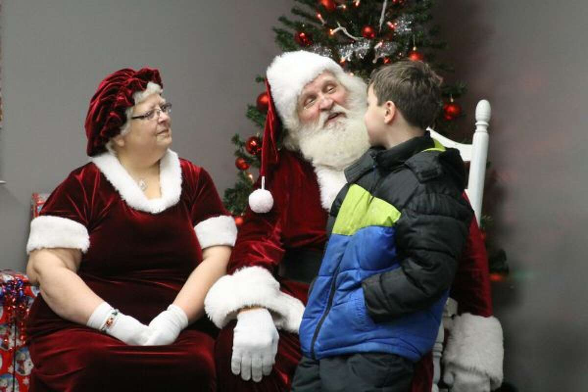 RJ McBrian, of Bear Lake, talks with Santa on Saturday at Dickson Township Fire Hall. (Michelle Graves/News Advocate)