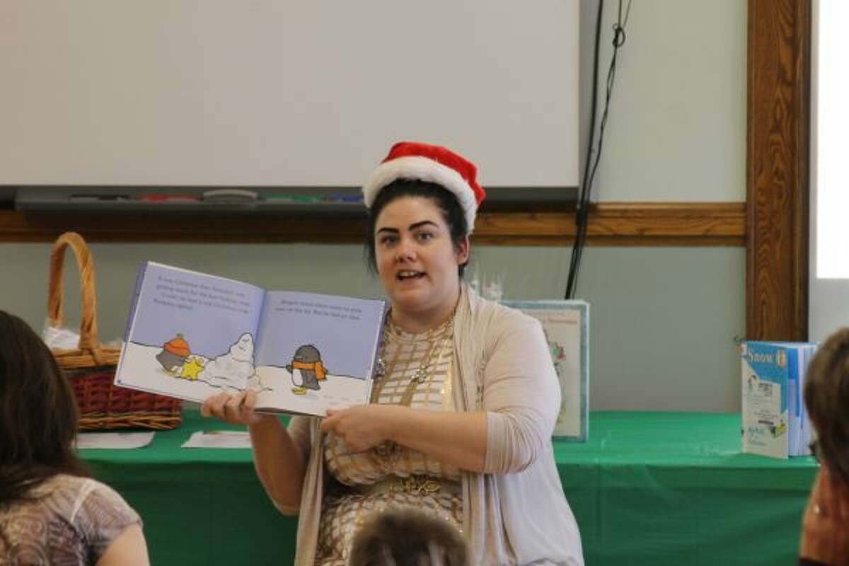 """Miss Julie reads a story to children at the Manistee Library on Saturday during the """"Santa is Coming"""" event. (Michelle Graves/News Advocate)"""