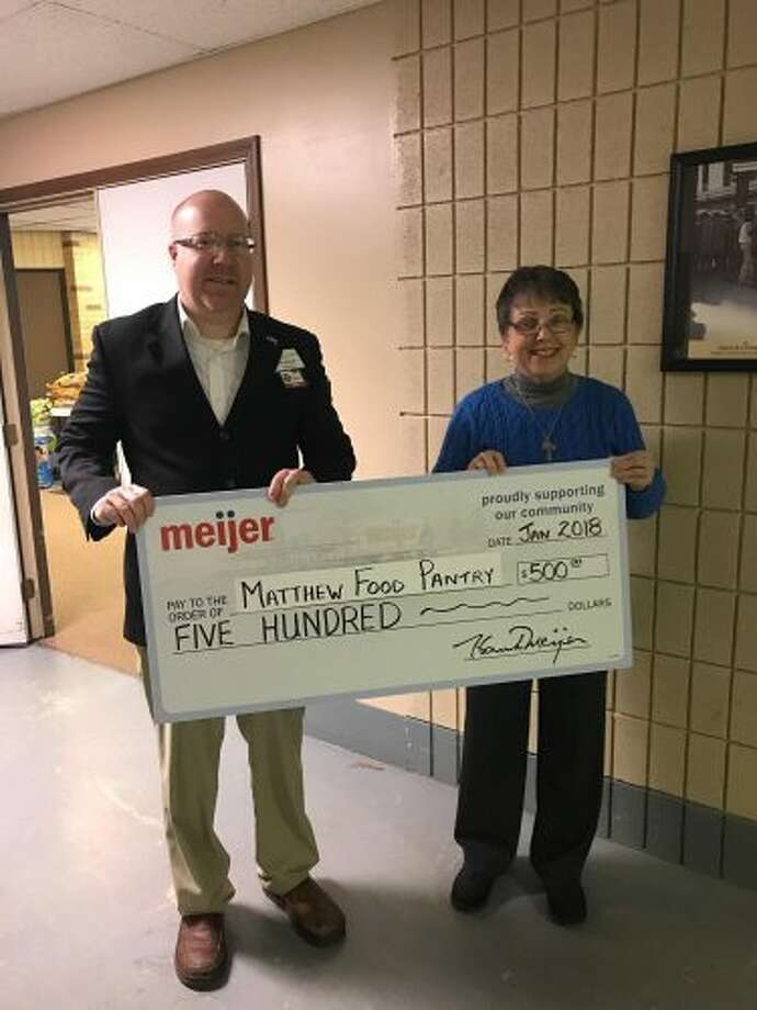 Meijer donated $500 to Matthew Food Pantry for its winter needs. Pictured are Ken Babcock, Meijer store director, and Joan Gamache, food pantry leader.