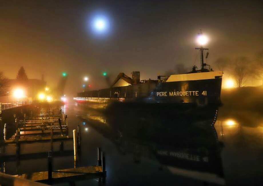 Tug Undaunted and barge Pere Marquette 41 travel through the Manistee River Channel around 4 a.m. on Wednesday. (Courtesy Photo/Chris Franckowiak)