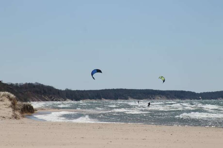 Matt Robke and Jeff Veach take off from First Street Beach on Saturday, kite surfing south on Lake Michigan near Merkey Road. The pair are from Grand Haven and have been kite surfing for many years. Their fathers, both of Manistee, were watching from shore. (Michelle Graves/News Advocate)