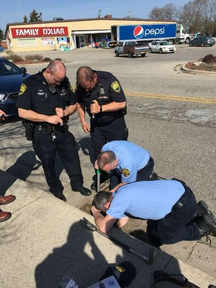 A group of Manistee City Police officers and Manistee Fire Department personnel work to save two ducklings from a storm drain on Tuesday. (Courtesy Photo/Heath Darling)