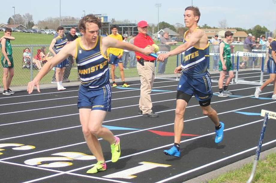 Manistee's Jacob Gustad (right) hands the baton off to Elliott Kamaloski (left) in the first race ever held on the track, the 4x800-meter relay. (Scott Yoshonis/News Advocate photos)