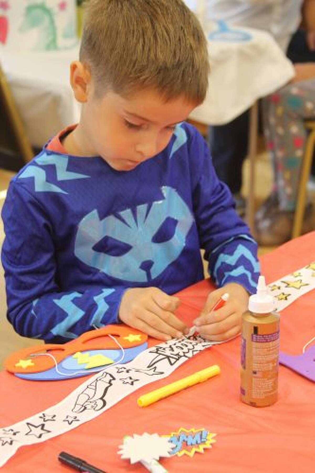 Marshall Bartos, of Manistee, colors a headband during the Superhero Party on Saturday at the Manistee County Library. (Michelle Graves/News Advocate)