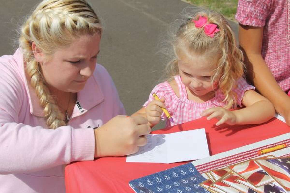 Sisters Jordan Jarvis and Raegan Whiteside, of Manistee, create a card of thanks, which will be sent to a veteran during the Red and Blue Barbecue at Green Acres of Manistee on Saturday. (Michelle Graves/News Advocate)