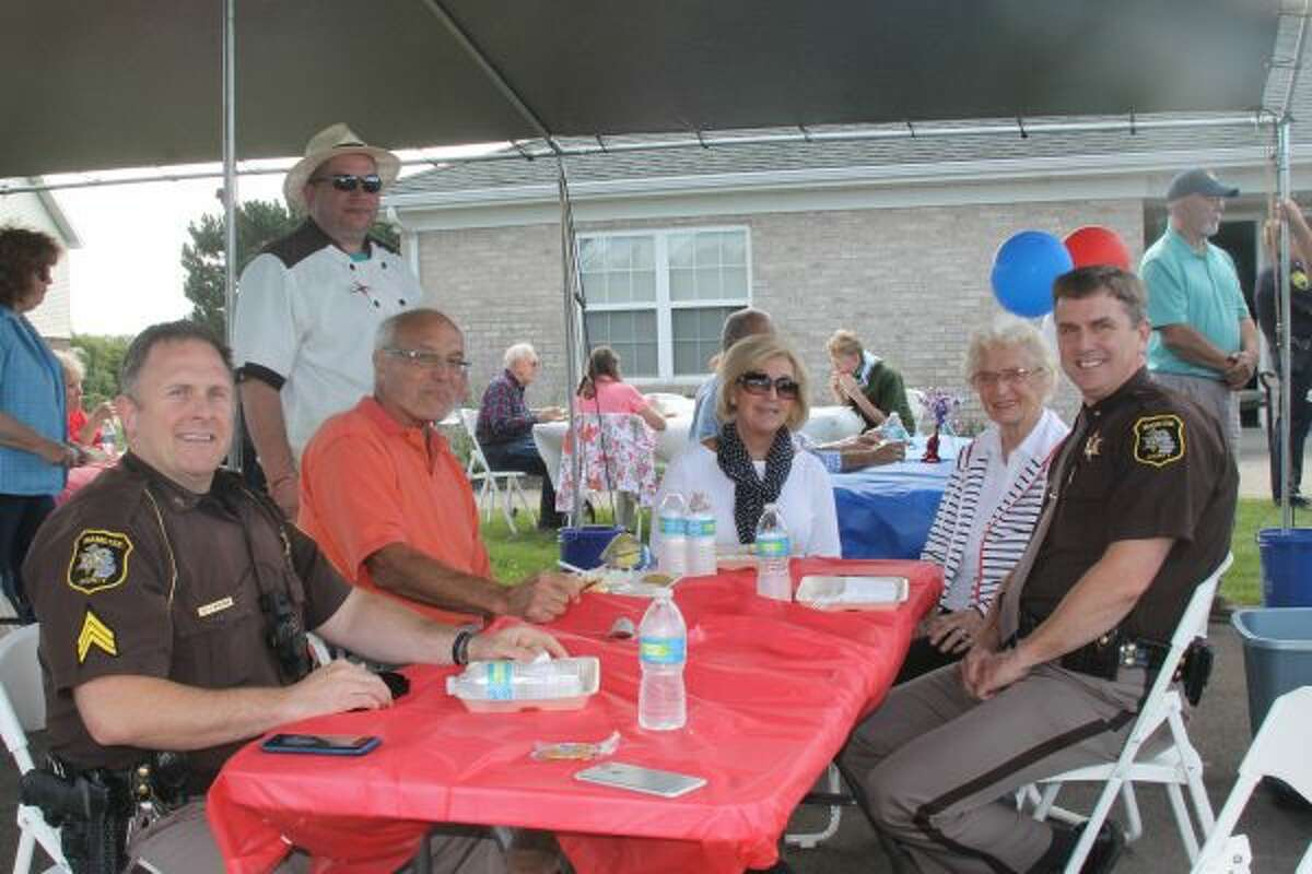 Law enforcement officers, including Manistee County Sheriff John O'Hagan (right) and deputies, were in attendance on Saturday during the Red and Blue Barbecue at Green Acres. (Michelle Graves/News Advocate)