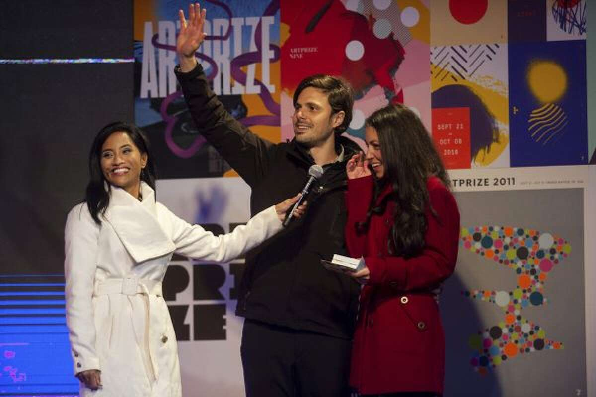 """Mariano Cortez waves as he and his wife Chelsea Nix are awarded the $200,000 public vote grand prize for their work """"THE STRING PROJECT,"""" during the 10th international ArtPrize awards ceremony in Grand Rapids, Mich., Friday, Oct. 5, 2018. (Neil Blake/The Grand Rapids Press via AP)"""