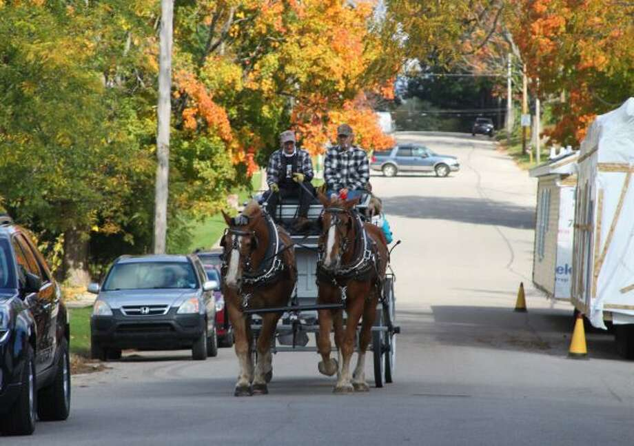 Families were able to take a wagon ride through Onekama during the Fall Festival. (Ashlyn Korienek/News Advocate)