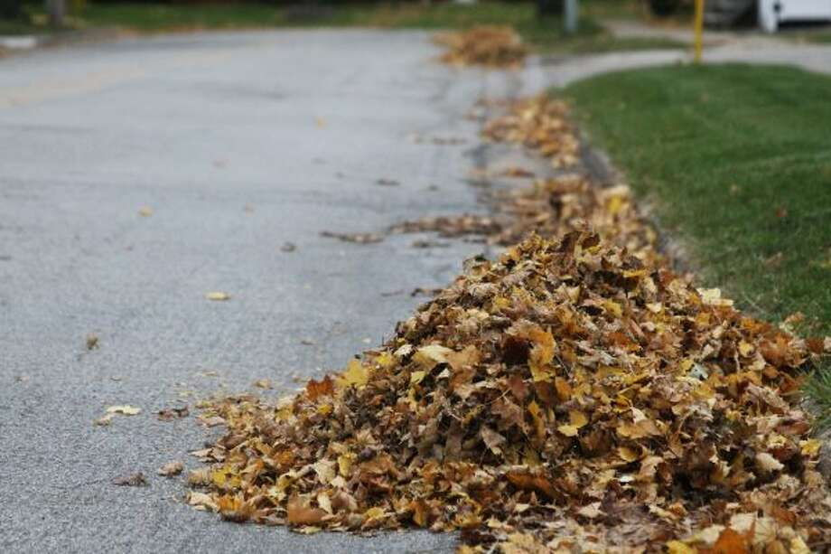 Leaves sit in piles along the streets of Manistee, waiting for removal. (Jane Bond/News Advocate)
