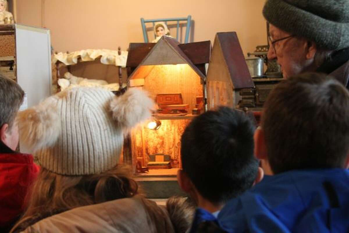 Manistee Catholic Central elementary students look at a dollhouse at the Manistee County Historical Museum on Wednesday. Volunteer Ray Fortier helped give the students tours. (Michelle Graves/News Advocate)