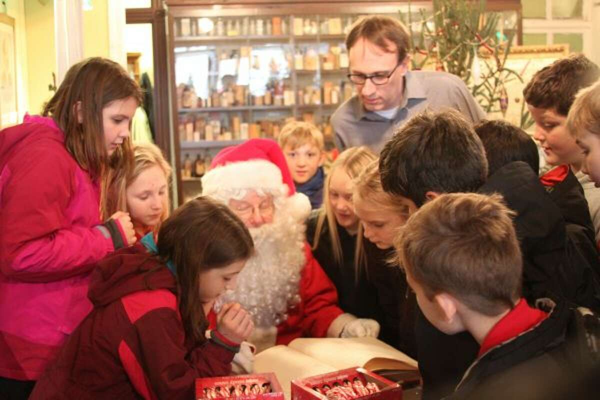 """Santa was the special guest at the Manistee County Historical Museum on Wednesday when students from Manistee Catholic Central came to visit. Several students, along with teacher Nick Fedder, look to see who is on Santa's """"naughty"""" or """"nice"""" list. (Michelle Graves/News Advocate)"""