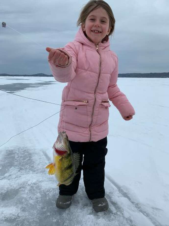 Hazel Sedelmaier, age 7, won the perch division with her 13.8-inch perch she caught on a tip-up with a golden shiner. She participated in the Manistee County Sport Fishing Association's first ever Fun Fish ice edition on Saturday. (Courtesy photo) Click through for more photos