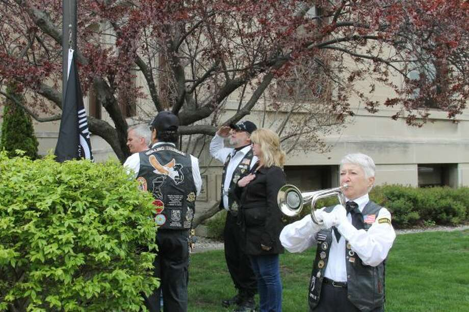 """Members of Rolling Thunder Chapter No. 1 and the community help to raise the POW/MIA flag on Friday near the veterans' memorial on the corner of First and Maple streets, while """"Taps"""" is played. (Michelle Graves/News Advocate) ***CLICK THROUGH FOR MORE PHOTOS***"""