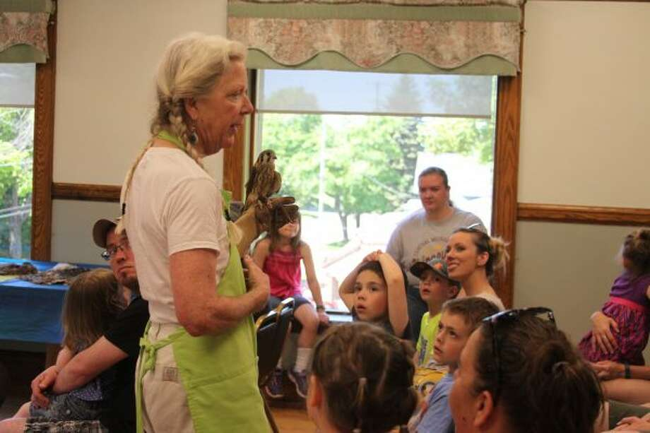 Children and adults were fascinated by the American kestrel falcon that Rebecca Lessard, from Wings of Wonder, showed off on Saturday during the Manistee Library's Summer Reading Program kickoff event. (Michelle Graves/News Advocate) ***CLICK THROUGH FOR MORE PHOTOS***