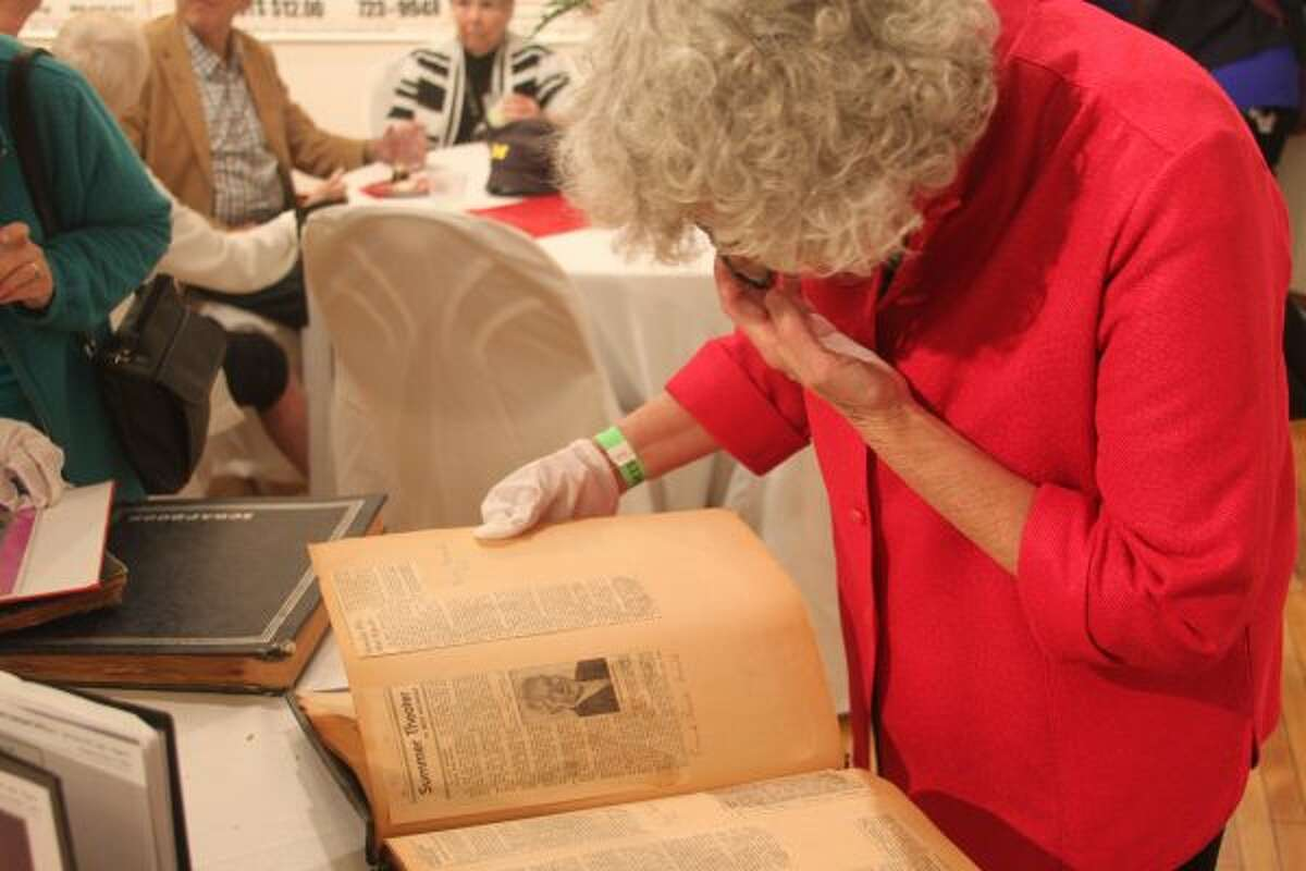 Attendees flip through scrapbooks documenting 80 years of memories made with the Manistee Civic Players. (Scott Fraley/News Advocate)