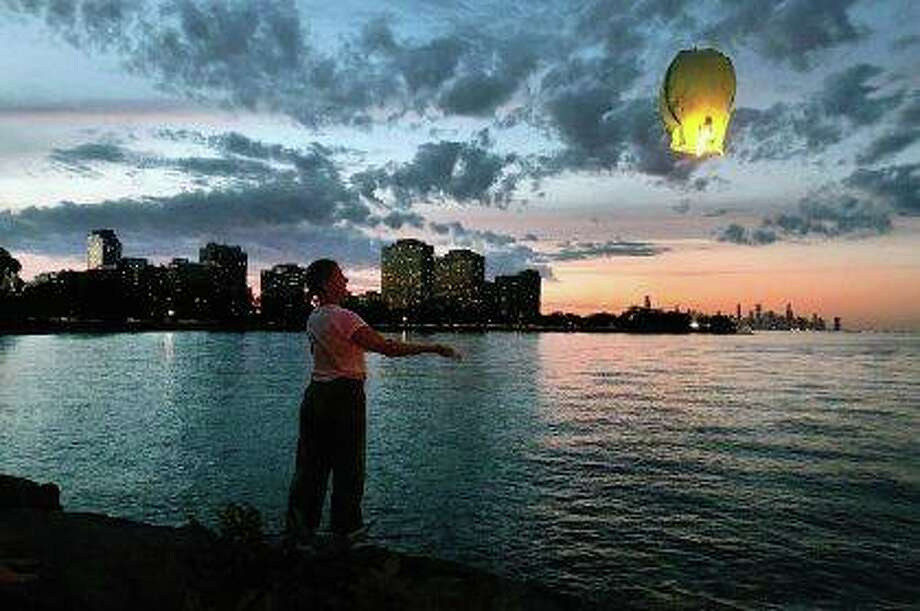 Elizabeth Hinker releases a wish lantern at sunset over Lake Michigan. Commonly known as sky lanterns, the small hot air balloons are made of paper and often are used for celebrations, memorials and making wishes. Photo: Charles Rex Arbogast | AP